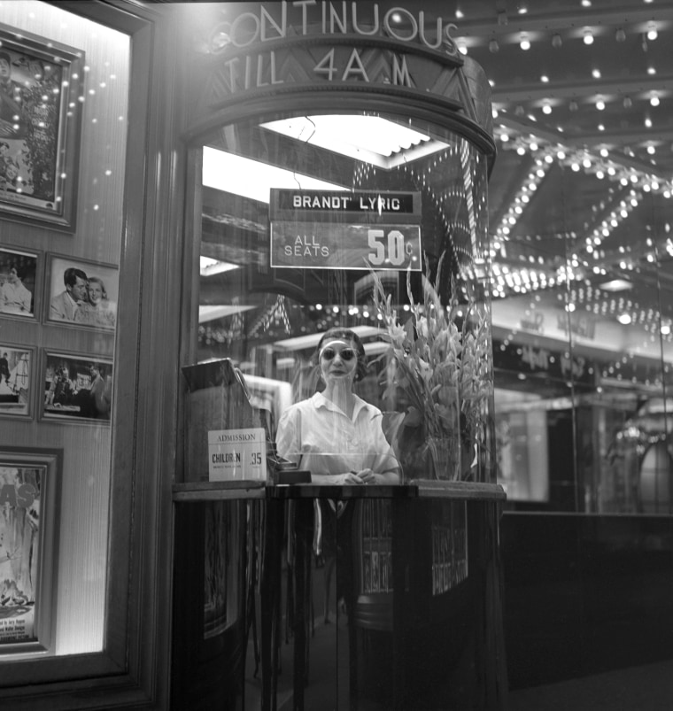 A woman peers out from a ticket booth of a movie theater in New York's Times Square in 1954. One thing that hasn't endured since Frank Larson took these photos: the price of a ticket.