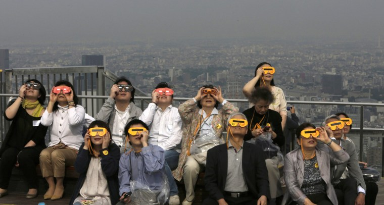 Image: People watch an annular solar eclipse at a rooftop of Roppongi Hills complex in Tokyo
