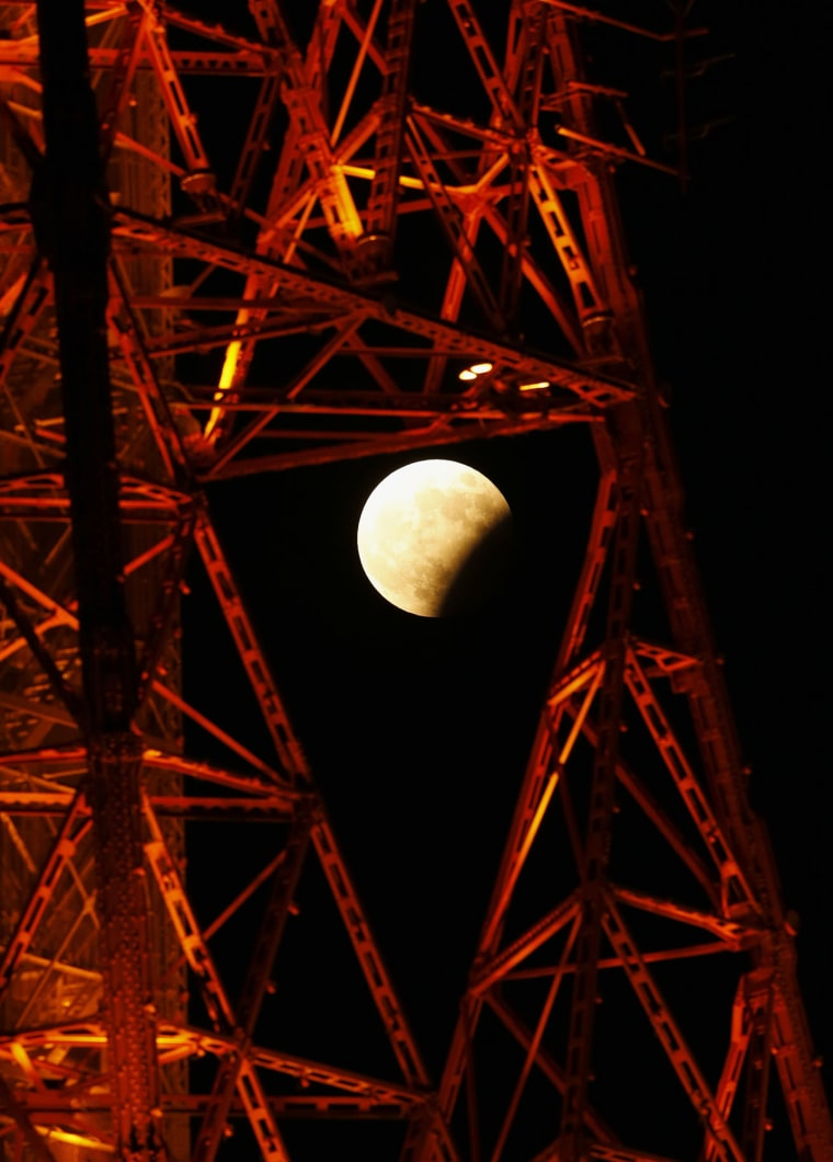 Image: A partial lunar eclipse is seen through the Sapporo TV Tower in Sapporo