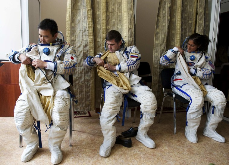 Image: Russian cosmonaut Malenchenko, Japanese astronaut Hoshide and U.S. astronaut Williams prepare their space suits during a training exercise at the Star City space centre outside Moscow