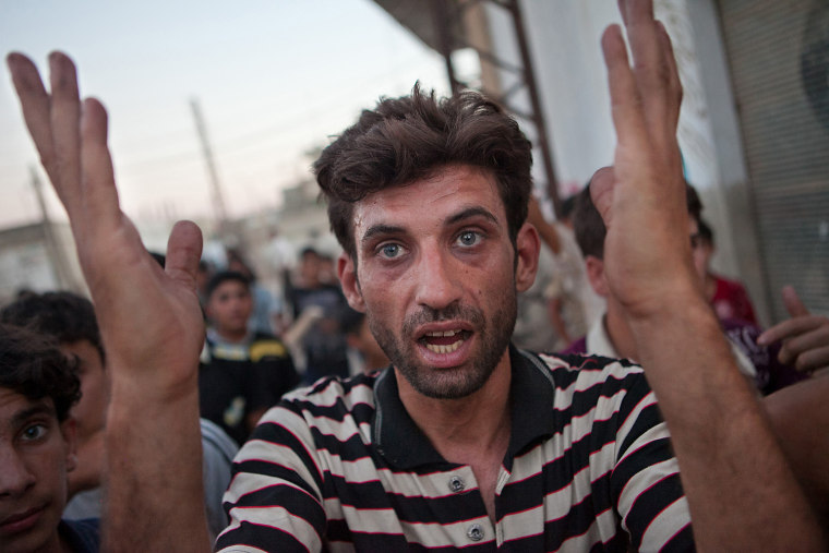 Image: A resident gestures in the Syrian village of Treimsa, where more than 150 people were killed last week