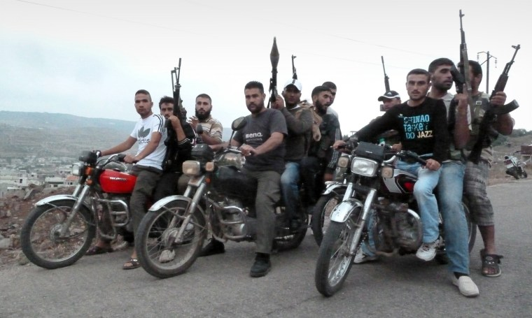 Image: Members of the Free Syrian Army ride mot