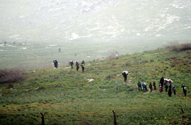 Image: Syrian refugees walk across a feild on the Syrian side of the border before crossing into Turkey