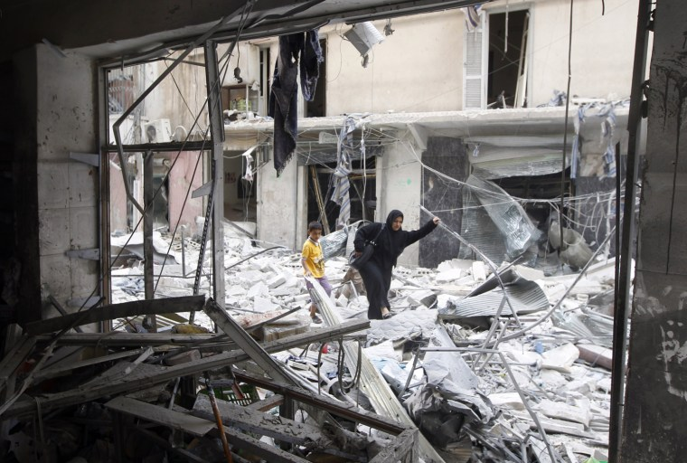 Image: A woman walks through rubble from a building destroyed by shelling from forces loyal to Syrian President Bashar Al-Assad in downtown Aleppo