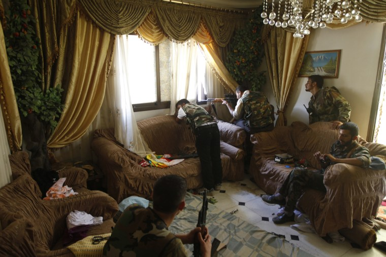 Image: A Free Syrian Army fighter fires his sniper rifle from a house in Aleppo
