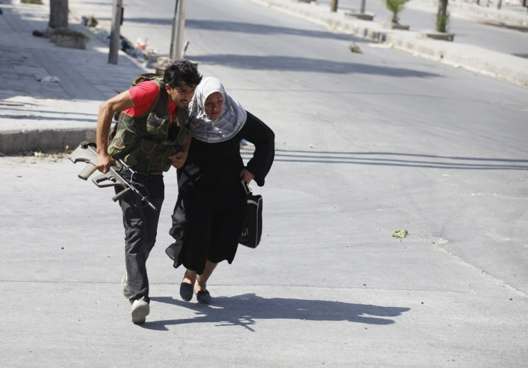 Image: A Free Syrian Army fighter helps a woman to run across a street during clashes in Aleppo
