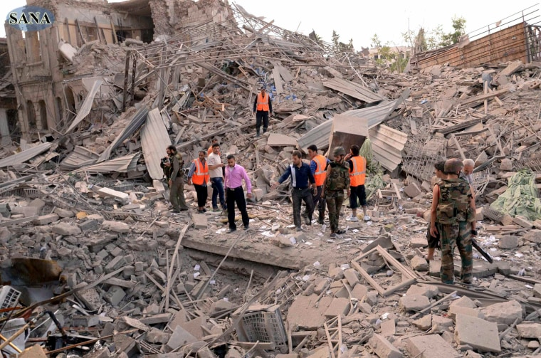 Image: Men stand amid wreckage, after three blasts ripped through Aleppo's main Saadallah al-Jabari Square. Picture released by the government-run Syrian Arab News Agency.