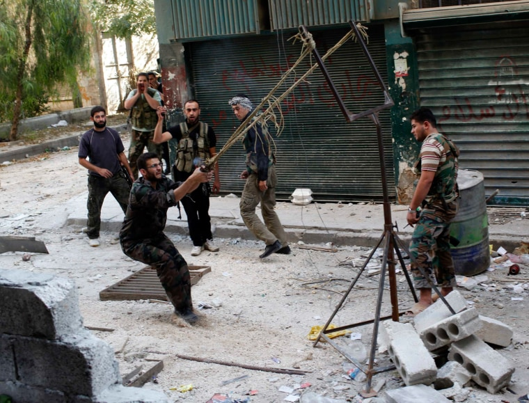 Image: Members of the Free Syrian Army use a catapult to launch a homemade bomb during clashes with pro-government soldiers in the city of Aleppo