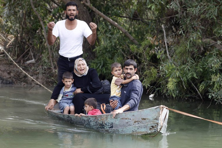 Image: A Syrian family cross to Turkey by boat over the Orontes river on the Turkish-Syrian border near the village of Hacipasa in Hatay province