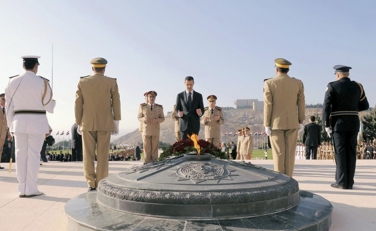 Image: Handout photo of Syria's President al-Assad praying after placing flowers at the Tomb of the Unknown Soldier in a ceremony to mark the 39th anniversary of the 1973 October War with Israel, in Damascus