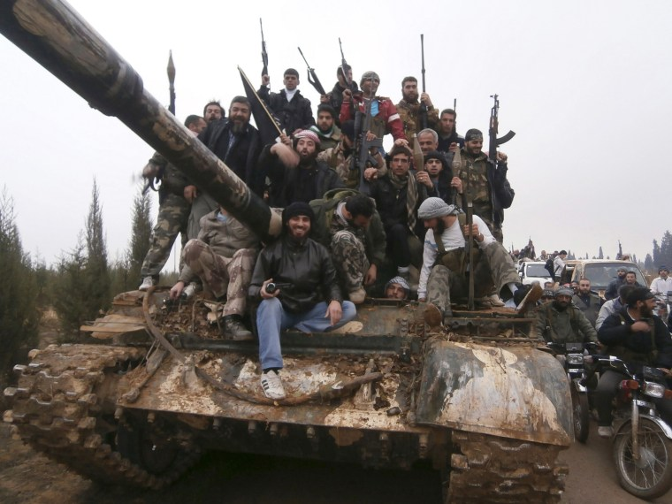 Image: Free Syrian Army fighters pose on a tank, which they say was captured from the Syrian army loyal to President Bashar al-Assad, after clashes in Qasseer