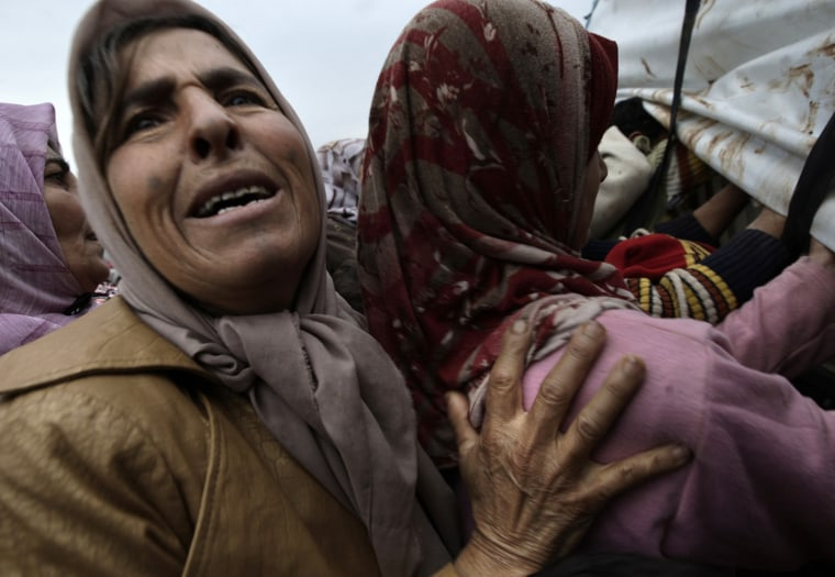Image: A woman who fled her home cries while asking for a pillow and a blanket at a distribution at a camp for displaced Syrians, in the village of Atmeh, Syria.