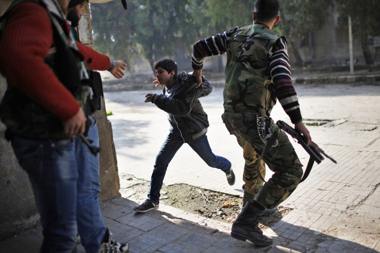 Image: A Free Syrian Army fighter pulls a boy off the street as a sniper fires during fighting with forces loyal to Syrian President Bashar el-Assad in Aleppo city