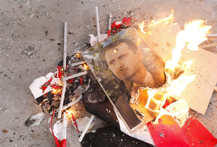Image: Pictures of Syria's President Bashar al-Assad and Syrian flags burn after being set on fire by Free Syrian Army fighters in Ouwayjah village in Aleppo