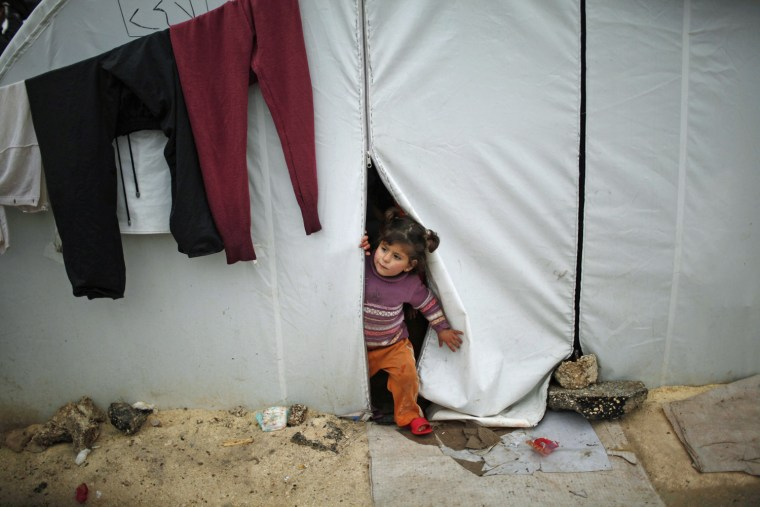 Image: A Syrian refugee child looks out of her family tent at Bib Salam refugee camp in Syria near the Turkish border