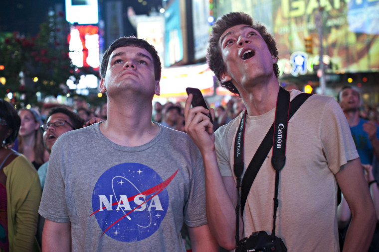 """Image: Jasper Goldberg, 22, and Andreas Bastian, 22, watch a live broadcast of the NASA Mission Control center, as the planetary rover """"Curiosity"""" lands on Mars, in Time Square"""