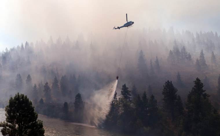 Image: A helicopter drops water taken from the adjacent Yakima River onto a wildfire near Cle Elum, Wash.