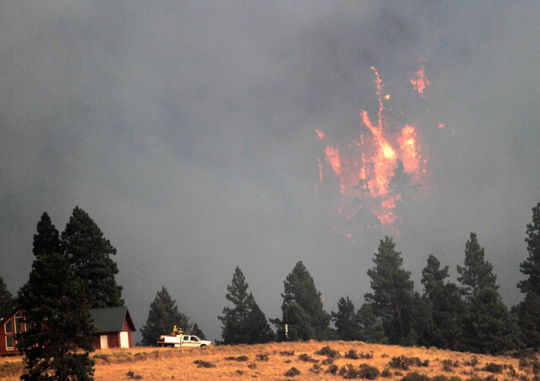 Image: Firefighters protect home threatened by Taylor Bridge Fire outside of  Cle Elum, Washington