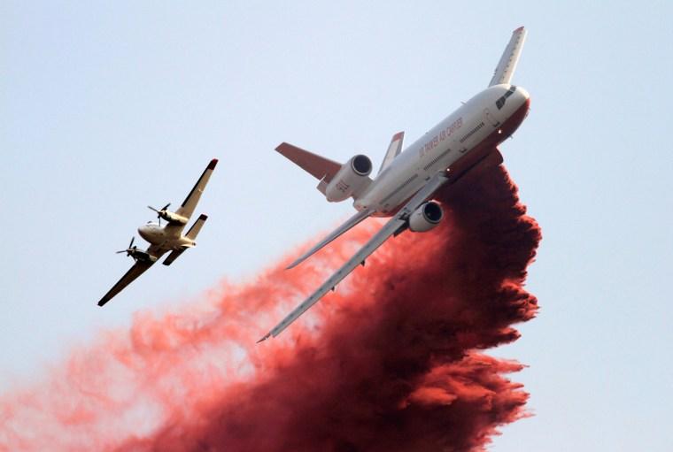 Image: Firefighting tanker plane drops fire retardant on homes threatened by Taylor Creek Fire outside Cle Elum, Washington