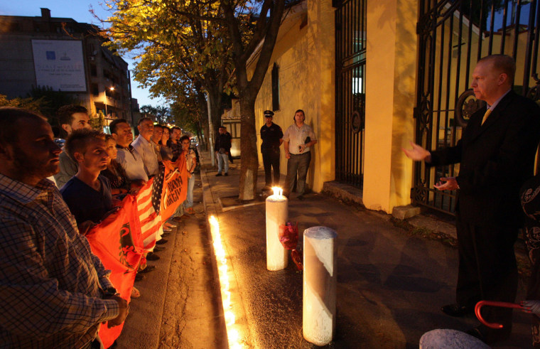 Image: Albanian youths holding a candlelight vigil in front of the US Embassy in Tirana