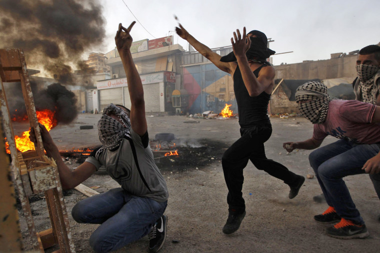 Image: Palestinian youths throw stones towards Israeli border police (not seen)  in the Shuafat refugee camp in the West Bank near Jerusalem