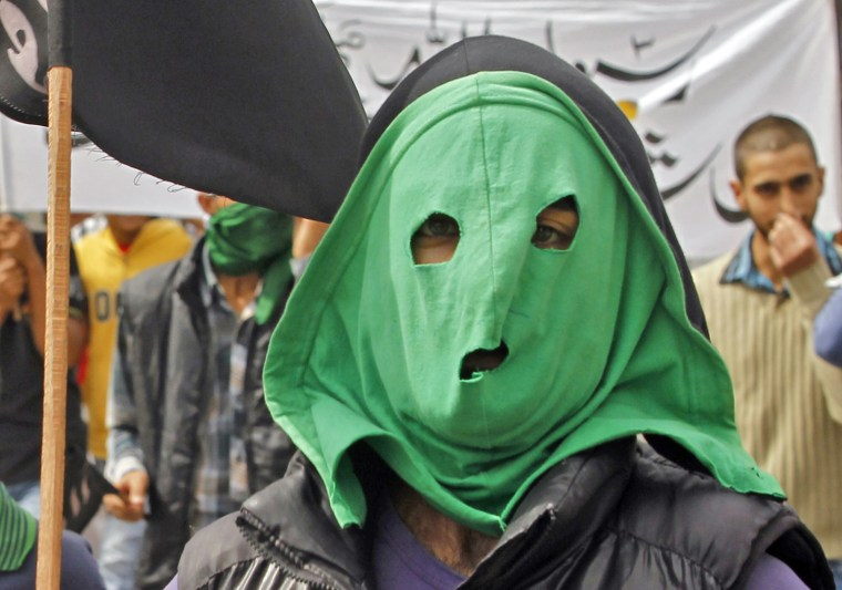 Image: A masked youth attends a strike in Srinagar
