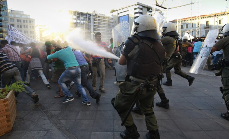 Image: Riot police use tear gas as they try to disperse Muslim protesters during a rally in central Athens