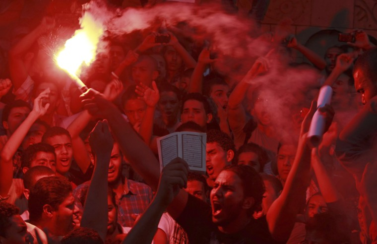 Image: People shout slogans and light flares in front of the U.S. embassy during a protest in Cairo