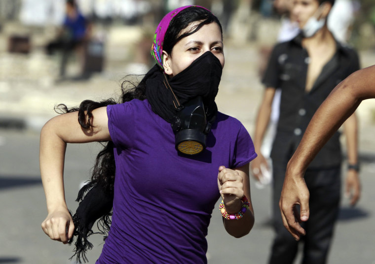 Image: A protester runs from tear gas released by riot police during clashes along a road which leads to the U.S. embassy, in Cairo