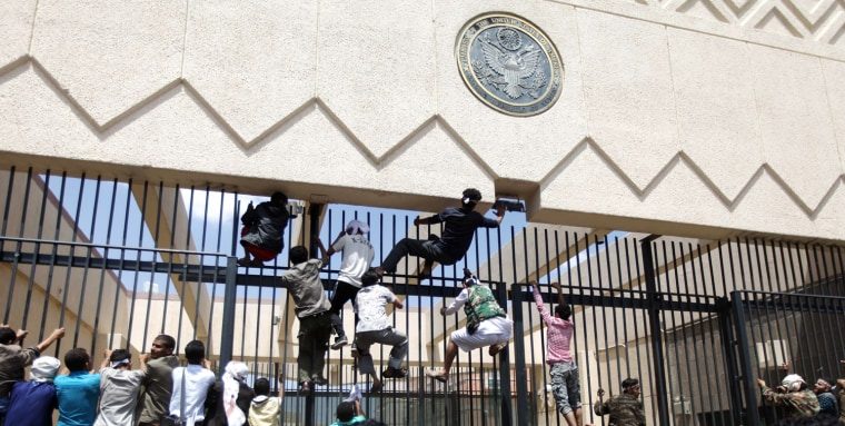 Image: Protesters climb a fence at the U.S. embassy in Sanaa, Yemen.