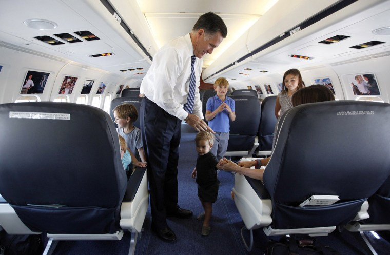 Image: U.S. Republican presidential nominee Romney pats the head of his grandson Sawyer during a tour of his campaign plane in Salt Lake City