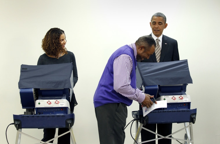 Image: U.S. President Barack Obama looks up from casting his early vote as a poll worker receives a phone call at the Martin Luther King Community Center in Chicago