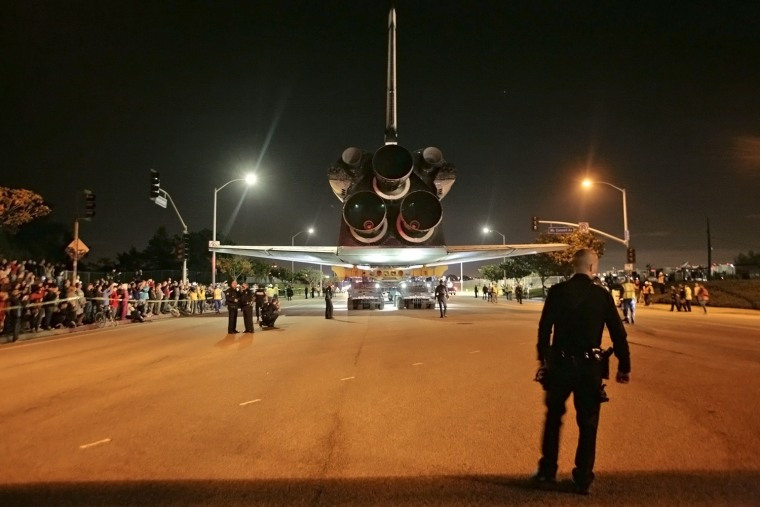 Image: A police officer stands near space shuttle Endeavour as it leaves Los Angeles International Airport and is transported on city streets to the California Science Center in Los Angeles