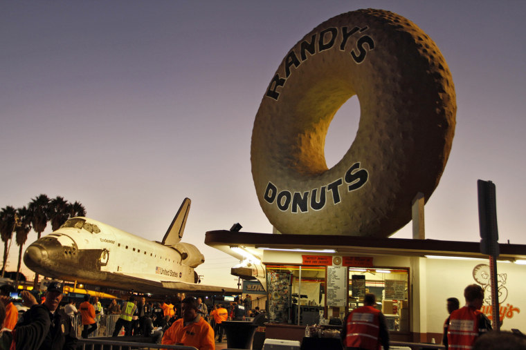 Image: Space Shuttle Endeavour stops in front of Randy's Donuts as it's transported on Manchester Avenue in Los Angeles, California
