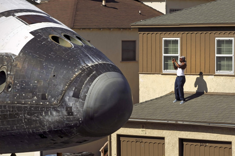 Image: A man takes a photo as Space Shuttle Endeavour travels to the California Science Center in Inglewood, Los Angeles