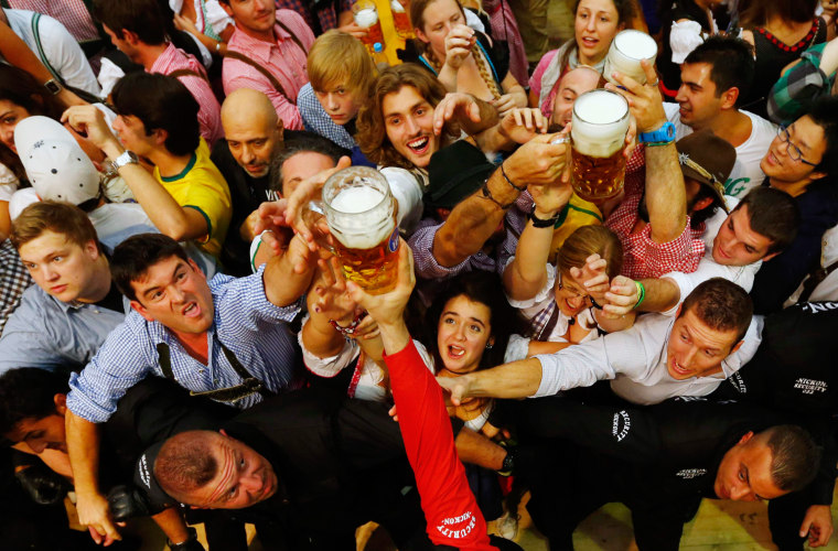 "Image: Revellers reach out for the first beer in the traditional one-liner ""Masskrug"" beer mugs at  the opening day of the Munich Oktoberfest at the Theresienwiese in Munich"