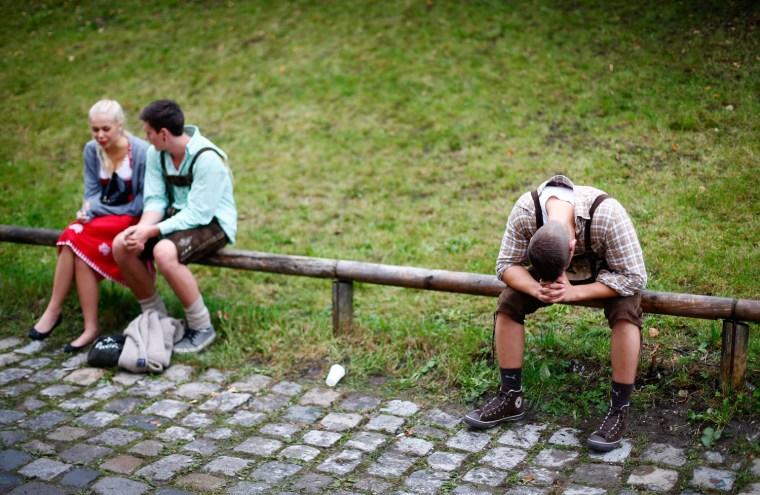 Image: Revellers have a break from drinking at the Munich Oktoberfest at the Theresienwiese in Munich