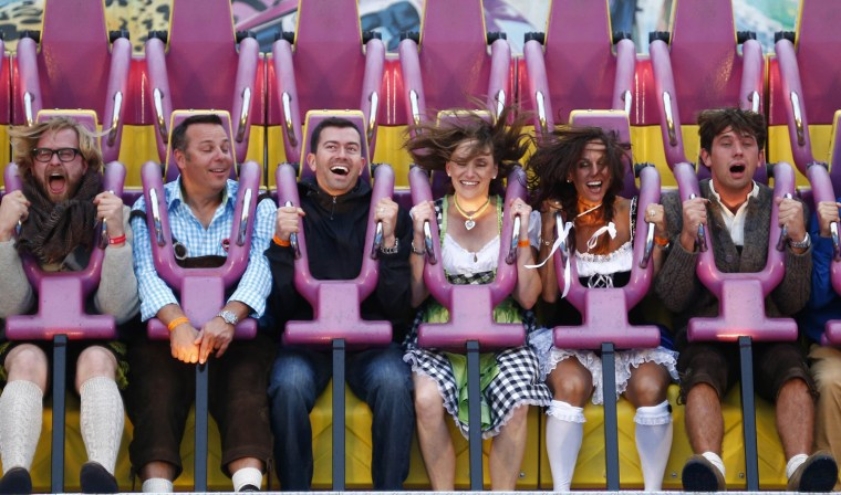 Image: Revellers enjoy a ride in a roller coaster at the Munich Oktoberfest at the Theresienwiese in Munich