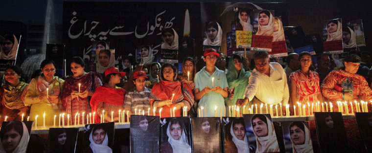 Image: People light candles alongside pictures of Malala Yousufzai at a school in Lahore