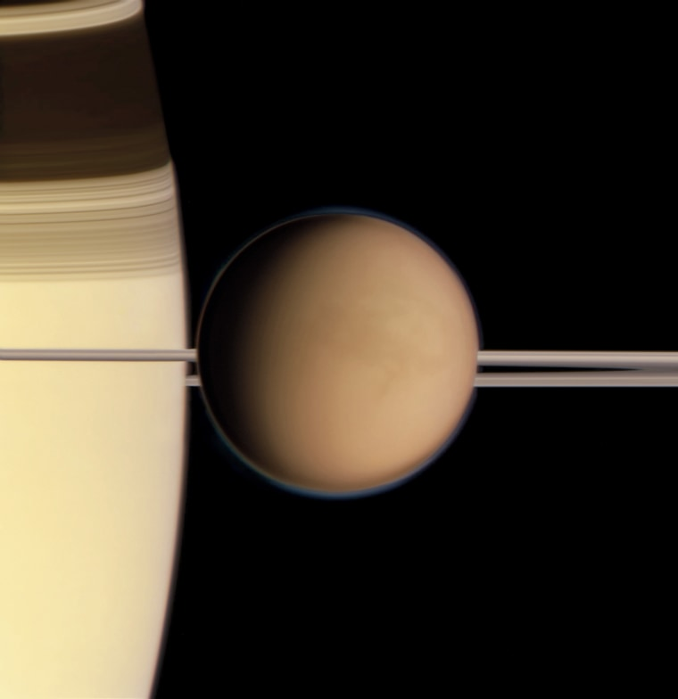 Titan in front of Saturn's rings and limb in this image made by the Cassini spacecraft on May 21, 2011. The features here barely visible through the moon's dense atmosphere could not be seen by the naked eye; the image is partly the result of filters capable of cutting through Titan's opaque murk.