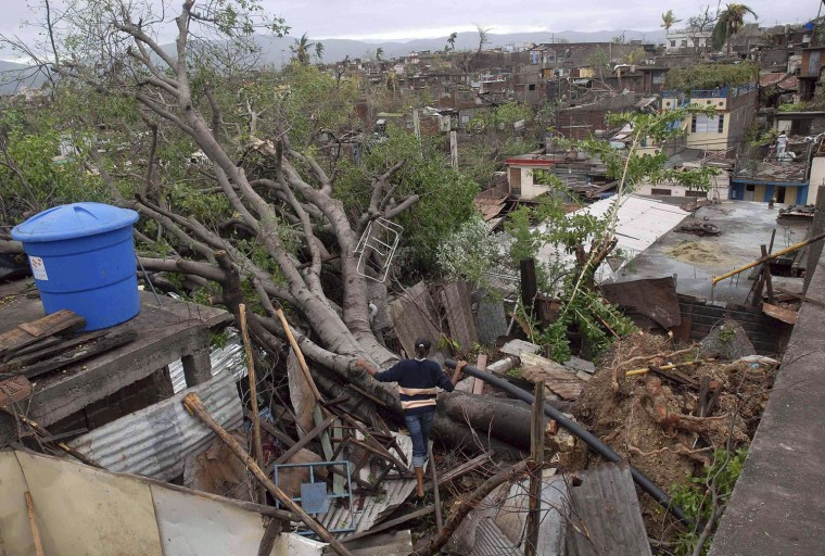 Image: A woman looks at a fallen tree on top of her house after Hurricane Sandy hit Santiago de Cuba