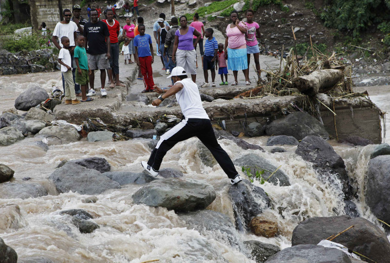 Image: Residents of Kingston try to cross the Hope River after a bridge was washed out by Hurricane Sandy