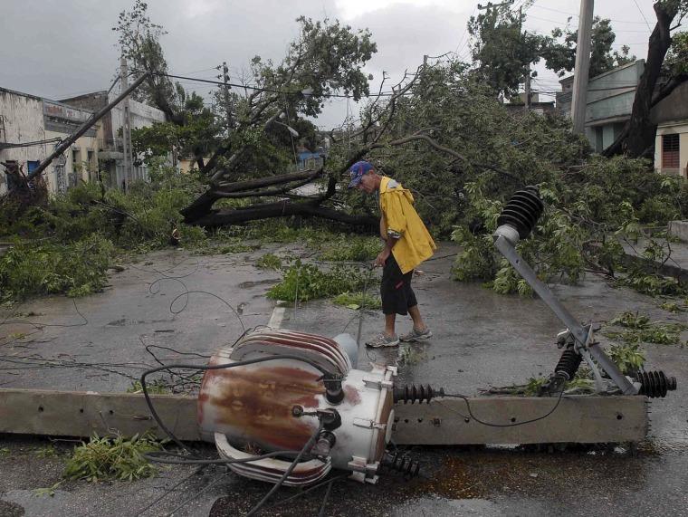 Image: A man walks near a damaged power line in Santiago de Cuba