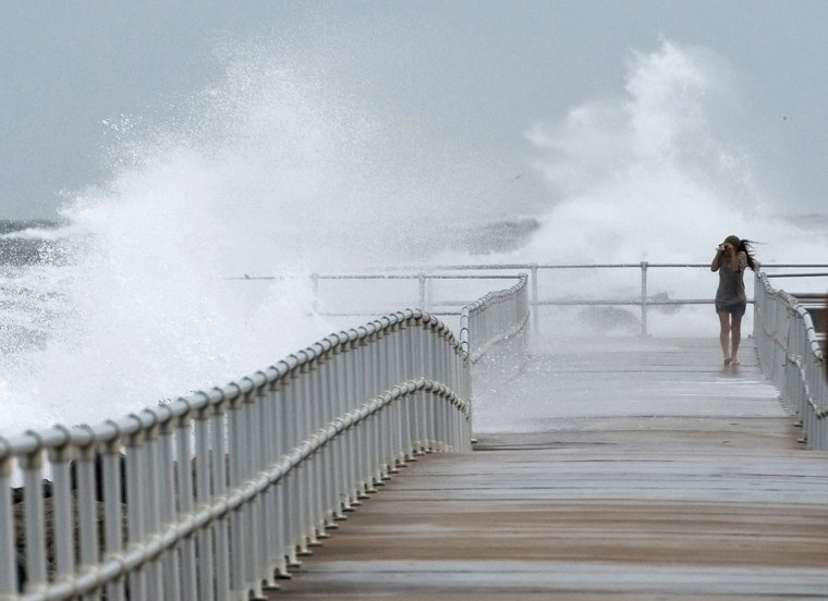 Image: Jean Marie Brennan walks along the jetty at Lighthouse Point Park as Hurricane Sandy passes offshore in Ponce Inlet