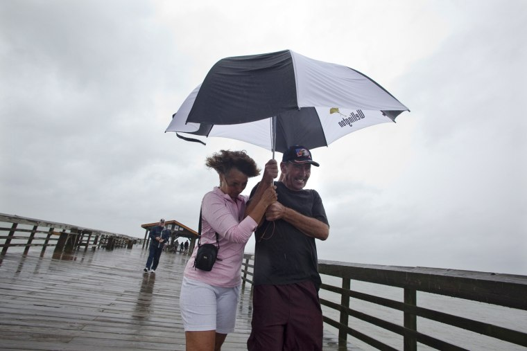 Image: Tim and Jo Ann Griffith struggle to hold on to their umbrella as they walk the pier at Myrtle Beach State Park