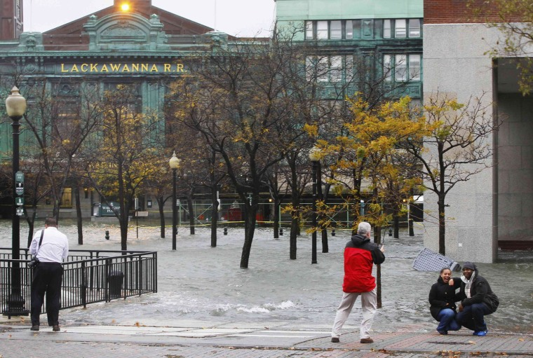 Image: People have their picture taken as water from Hudson River spills over a wall flooding the street in front of train station in Hoboken, New Jersey