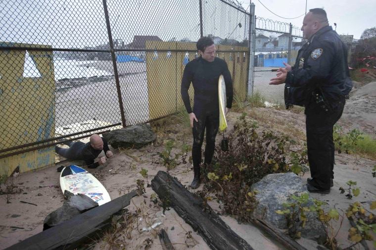 Image: A police office questions two surfers as they climb under a fence after surfing in Coney Island in New York