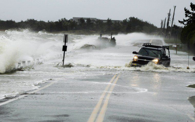Image: A truck drives through water pushed over a road by Hurricane Sandy in Southampton