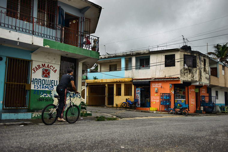 Thurs, Oct 25. During a break in the storm, A man bikes thorough the streets of Santo Domingo's Olymo neighborhood.