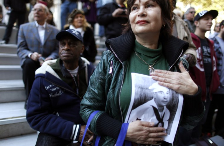 Image: Carol Romeo holds up a photo of her father, Jack Romeo, a World War II veteran during the Veterans Day Parade in New York